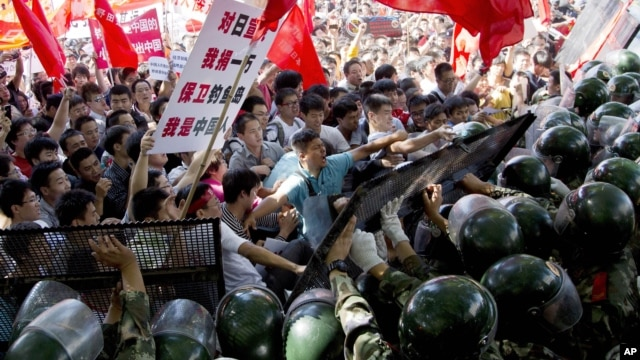Chinese demonstrators clash with policemen during an anti-Japan protest outside the Japanese Embassy in Beijing, China, September 15, 2012.
