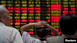 Investors look at an electronic board showing stock information at a brokerage house in Shanghai, China, June 20, 2018.