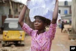 A woman carry bags of water she bought on a street in Baruwa Lagos, Nigeria, March 22, 2017.