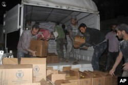FILE - This photo provided by the Syrian anti-government activist group Local Council of Daraya City, which has been authenticated based on its contents and other AP reporting, shows Syrian citizens load food and other supplies from a truck that entered the besieged town of the rebel-held suburb of Daraya, southwest of Damascus, Syria, June 10, 2016.