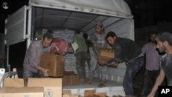 Warga Suriah mengeluarkan bantuan makanan dan bantuan lainnya dari truk Bulan Sabit Merah Suriah dan PBB di kota Daraya, pinggiran barat daya Damaskus, Jumat dini hari (10/6).