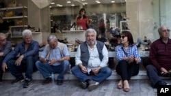 希腊退休人员坐在雅典一家鞋店前等候参加集会,抗议政府的国际债务救助计划的改革。(2018年4月25日)