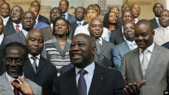 Incumbent President Laurent Gbagbo, center, gestures during a photo opportunity with his newly-named cabinet, with Prime Minister N'Gbo Gilbert Marie Ake, front left, at the presidency in Abidjan, Ivory Coast, Dec 7, 2010