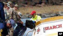 Petugas keamanan perairan menyerahkan beberapa barang ke anggota militer di pusat komando, 16 Agustus 2017 di Haleiwa, Hawaii. Sebuah helikopter angkatan darat membawa 5 orang penumpang jatuh beberapa mil lepas pantai utara Oahu, Selasa pekan lalu. (Foto:dok)