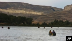 FILE - A group canoes through the Upper Missouri River Breaks National Monument near Fort Benton, Montana, Sept. 19, 2011. The status of many national monument areas has been ordered reviewed by President Donald Trump.