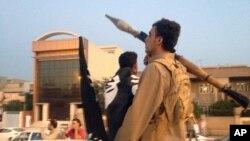 ພວກນັກຕໍ່ສູຸ້ ISIL ຂີ່ລົດໄປຕາມຖະໜົນຫຼວງ ໃນເມືອງ Mosul ໃນພາກເໜືອຂອງອີຣັກ ວັນທີ 23 ມິຖຸນາ 2014.