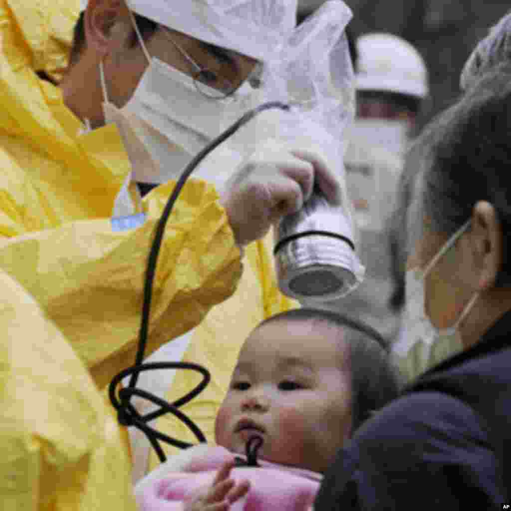 A baby is tested for radiation in Nihonmatsu, Fukushima Prefecture in northern Japan, March 15, 2011. Panic swept Tokyo on Tuesday after a rise in radioactive levels around an earthquake-hit nuclear power plant north of the city, causing some to leave the