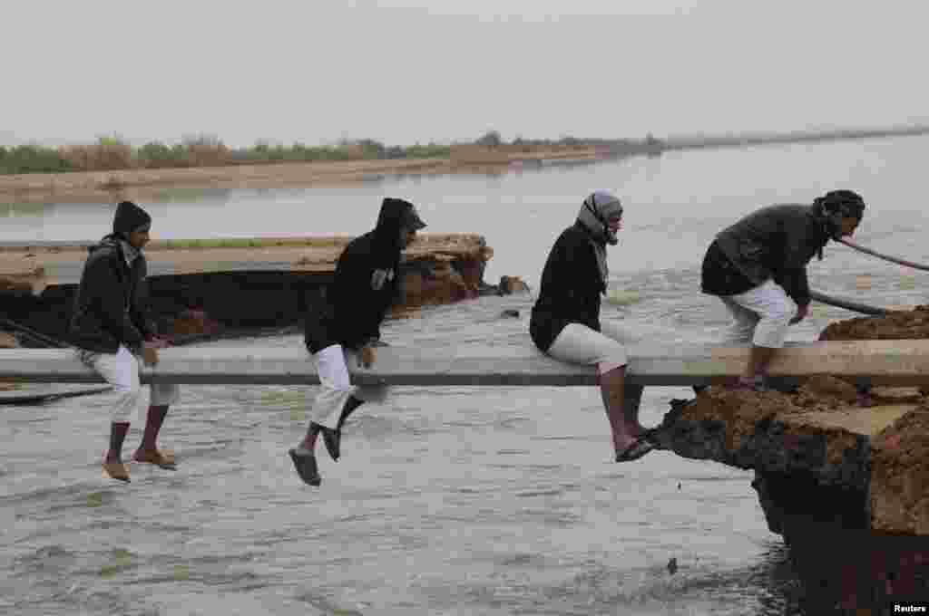People cross a flooded area after heavy rain in Tabuk, 1500 km (932 miles) from Riyadh, Saudi Arabia.