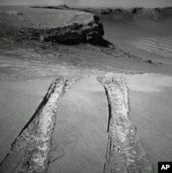 "NASA's Mars Exploration Rover Opportunity climbed out of ""Victoria Crater"" following the tracks it had made when it descended into the 800-meter-diameter (half-mile-diameter) bowl nearly a year earlier."