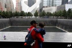 Un hombre y su hija observan la fuente norte en el World Trade Center en Nueva York durante la ceremonia recordatorai de los ataques terroristas de 2001 el martes, 11 de septiembre de 2018.