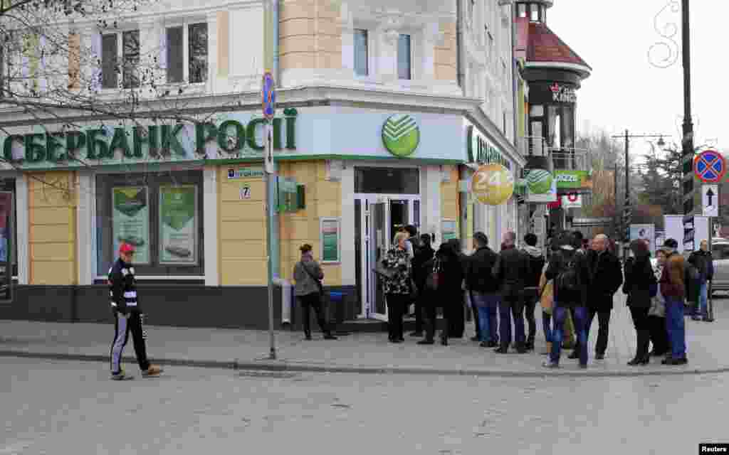 People stand in line as they wait to enter a branch of the Sberbank of Russia bank in the Crimean city of Simferopol, April 4, 2014.
