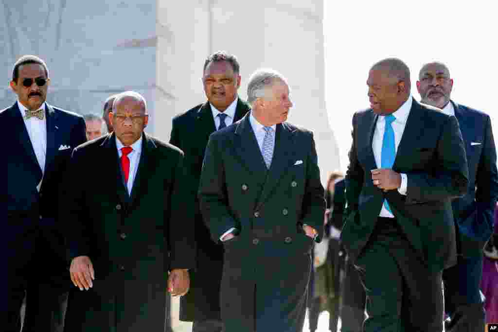 British Prince Charles tours the Martin Luther King, Jr. Memorial with President and CEO of the Martin Luther King, Jr. Memorial Project Foundation, Harry Johnson, second from right, Rev. Jesse Jackson, third from left, Dr. Ed Jackson, chief architect of the memorial, left, and President of the Tommy Hilfiger Corporate Foundation Guy Vickers, right, in Washington, March 18, 2015.