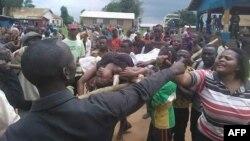 Des gens se disputent alors qu'une femme est transportée à l'hôpital de Beni, RDC, le 15 août 2016 après une vague de violences dans la région.
