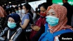Para penumpang mengenakan masker saat menunggu kereta di sebuah stasiun di Jakarta, 2 Maret 2020.