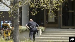 An Oakland police officer approaches the entrance to Oikos University in Oakland, Calif., Monday, April 2, 2012.