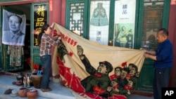 北京商販正在展示一面畫有中國前領導人毛澤東在文革時期的宣傳旗。 (2016年5月16日)
