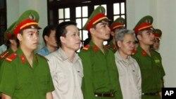 Ông Ðoàn Văn Vươn (thứ hai từ trái) và anh trai Đoàn Văn Sinh (thứ tư từ bên trái) bị đưa ra xét xử tại Tòa án Nhân dân thành phố Hải Phòng, ngày 2/4/2013.