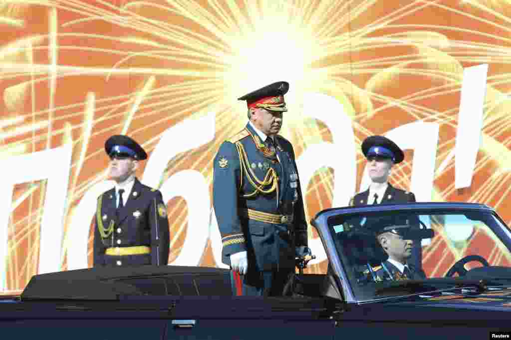 Russian Defense Minister Sergei Shoigu (C) reviews the troops during the Victory Day parade in Moscow's Red Square.