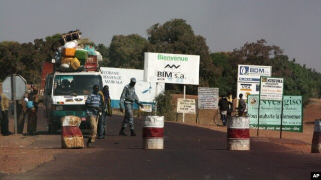 A public transport minibus is stopped by Malian soldiers at a checkpoint at the entrance to Markala, approximately 40 km outside Segou on the road to Diabaly, in central Mali, Jan. 14, 2013.