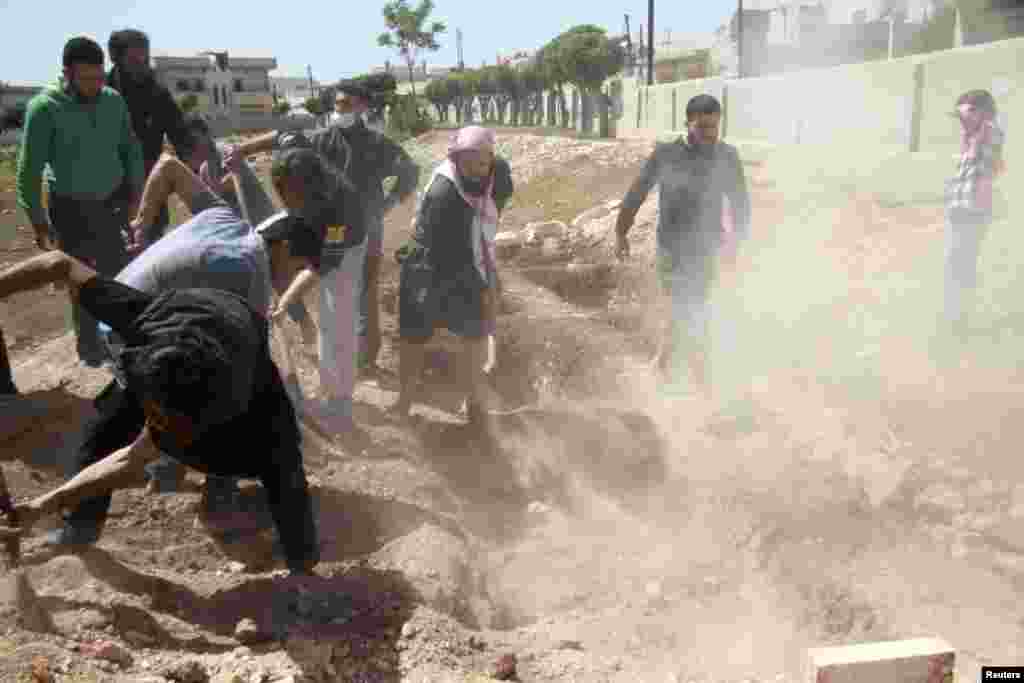 People bury a person activists said was killed by a barrel bomb dropped by forces loyal to Syria's President Bashar al-Assad in Kafarzita, in northern Hama countryside, April 23, 2014.