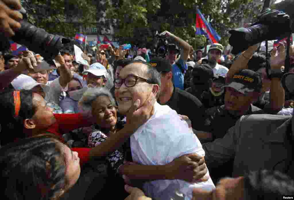Sam Rainsy (C), president of the opposition Cambodia National Rescue Party (CNRP), is surrounded by his supporters as he arrives at a protest at the Freedom Park in central Phnom Penh.