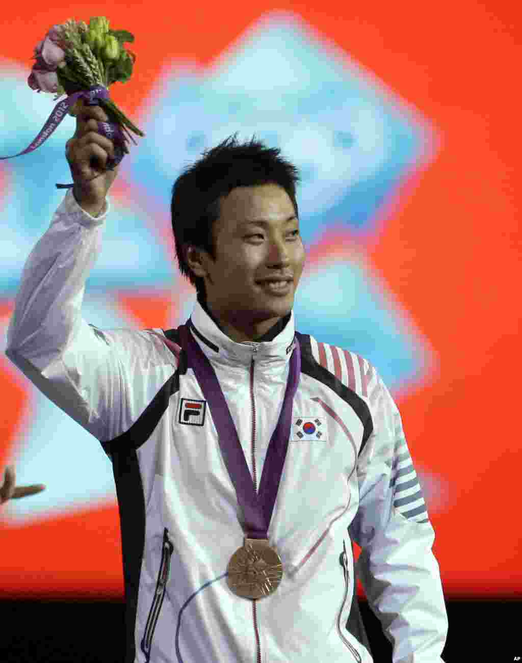 Bronze medalist Choi Byungchul of South Korea, waves to the crowd during the medals ceremony after the men's individual foil fencing competition at the 2012 Summer Olympics, July 31, 2012, in London.