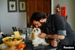 The Sharpville Show's lead singer Todd Sharpville cuddles dog Genghis as the group isolate together with their families and pets in a rented luxury estate.