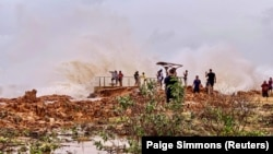 People watch as huge waves brought by Cyclone Veronica crash on the coast in Port Hedland, Western Australia, March 24, 2019, in this image obtained from social media.