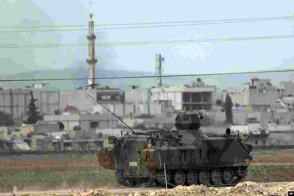 Backdropped by Kobani, in Syria, a Turkish forces armored vehicle patrols the border road in Mursitpinar, on the outskirts of Suruc, on the Turkey-Syria border, Oct. 14, 2014.