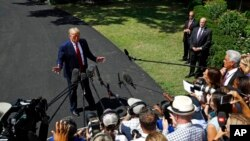 """特朗普总统在登上""""海军陆战队一号""""直升机前在白宫南草坪对媒体讲话。(2019年8月21日)"""