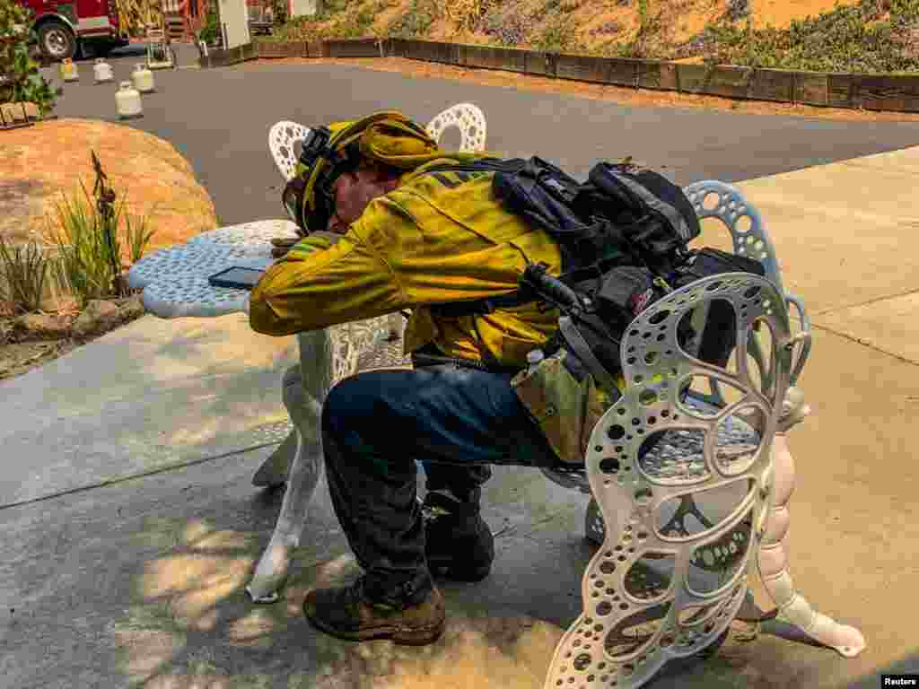 A firefighter rests during works to put out a fire in Alpine, California, in this picture obtained from social media.