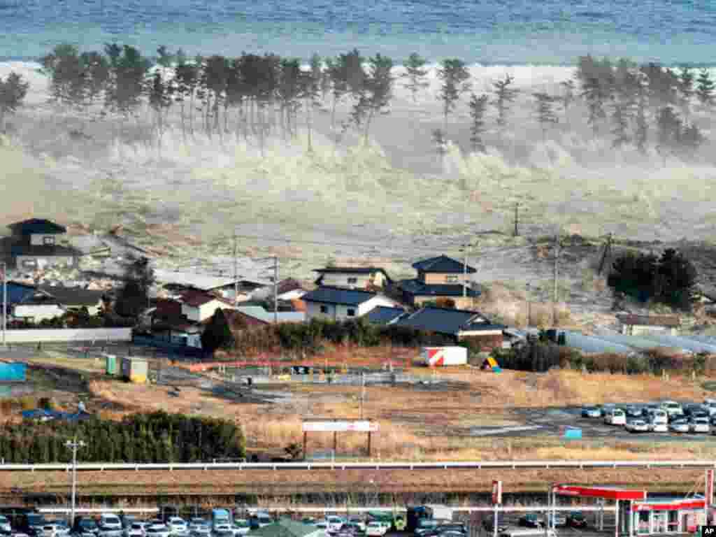 Hirarka Tsunami oo ku dhuftay xaafaddo ay dadku degan yihiin kaddib markii dhul-gariir xooggan uu ku dhuftay Natori, waqooyi bari Japan. March 11, 2011.