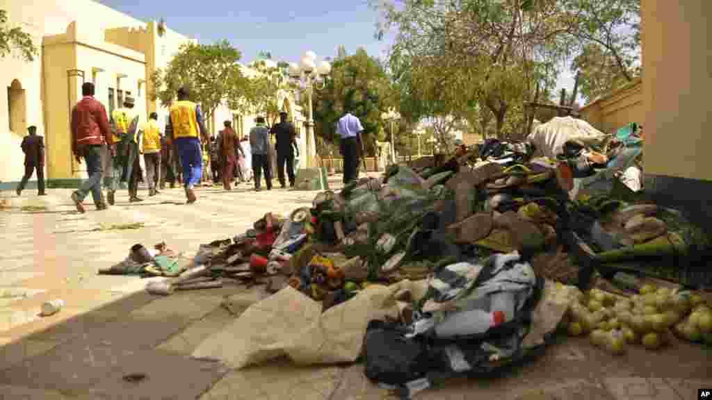 Quelques personnes marchent près de débris laissé par l'explosion d'une bombe à Kano, au Nigeria samedi 29 novembre 2014.