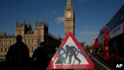 A road work sign stands on Westminster Bridge, near the Houses of Parliament and Elizabeth Tower, which houses the Big Ben bell in London, April 26, 2016. Officials say the chimes of Britain's Big Ben bell will fall silent for several months during a three-year restoration of Parliament's crumbling clock tower.