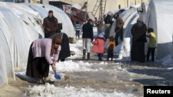 A Syrian refugee uses a toy shovel to remove snow from outside her tent at Bab al-Salam refugee camp in Syria near the Turkish border January 10, 2013.