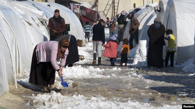 A Syrian refugee uses a toy shovel to remove snow from outside her tent at Bab al-Salam refugee camp in Syria, near the Turkish border, January 10, 2013.