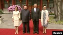中国国家主席习近平和夫人彭丽媛在北京钓鱼台国宾馆的养源斋前面同朝鲜国务委员会委员长金正恩和夫人李雪主合影。