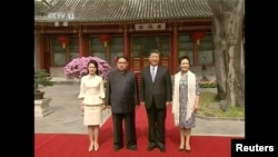 Pemimpin Korea Utara Kim Jong-un, istrinya Ri Sol Ju, Presiden China Xi Jinping dan istrinya Peng Liyuan, 28 Maret 2018. (Foto: CCTV via Reuters).
