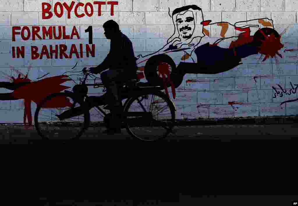 A man rides his bicycle past graffiti on a wall urging a boycott of the April 21 Formula One Bahrain Grand Prix with an image of Crown Prince Salman Al Khalifa in a racing car in Bar Bar, Bahrain.