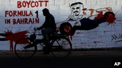 A man rides his bicycle past graffiti on a wall urging a boycott of the April 21 Formula One Bahrain Grand Prix with an image of Crown Prince Salman Al Khalifa in a racing car in Bar Bar, Bahrain, April 8, 2013.