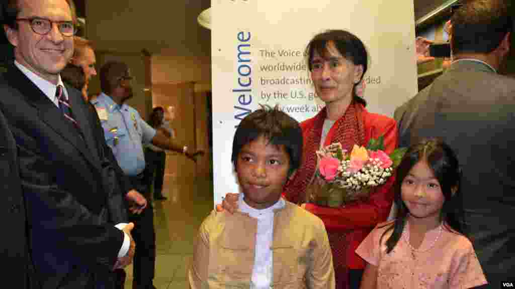VOA Director David Ensor (left) and two children of Burmese Service staff members offer flowers to Aung San Suu Kyi and pose for photographers.