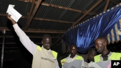 A poll worker holds up a ballot as vote counting begins in Kampala, February 18, 2011