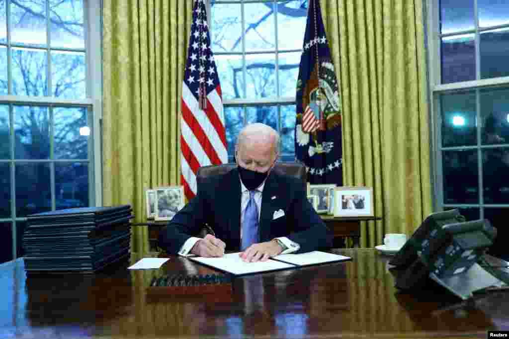 46-prezident Jo Bayden Oq uyda ilk farmonlarini imzolamoqda. Vashington shahri.