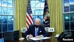 Rais Joe Biden akisaini amri za kiutendaji ofisini White House, Washington, DC, mara baada ya kuapishwa kuwa Rais wa 46 wa Marekani. January 20, 2021. REUTERS/Tom Brenner