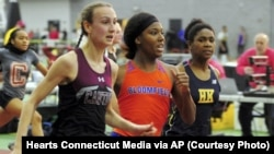 In this Friday, Feb. 14, 2020 photo, Canton High School's Chelsea Mitchell, left, beats Terry Miller, center, of Bloomfield, in the CIAC Class S track and field championships at Floyd Little Athletic Center in New Haven, Conn. (Christian Abraham/Hearst Connecticut Media via AP)