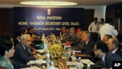 Officials of Pakistan, left, and India, right, sit on either side of a table during India-Pakistan talks in New Delhi, India, March 28, 2011. I
