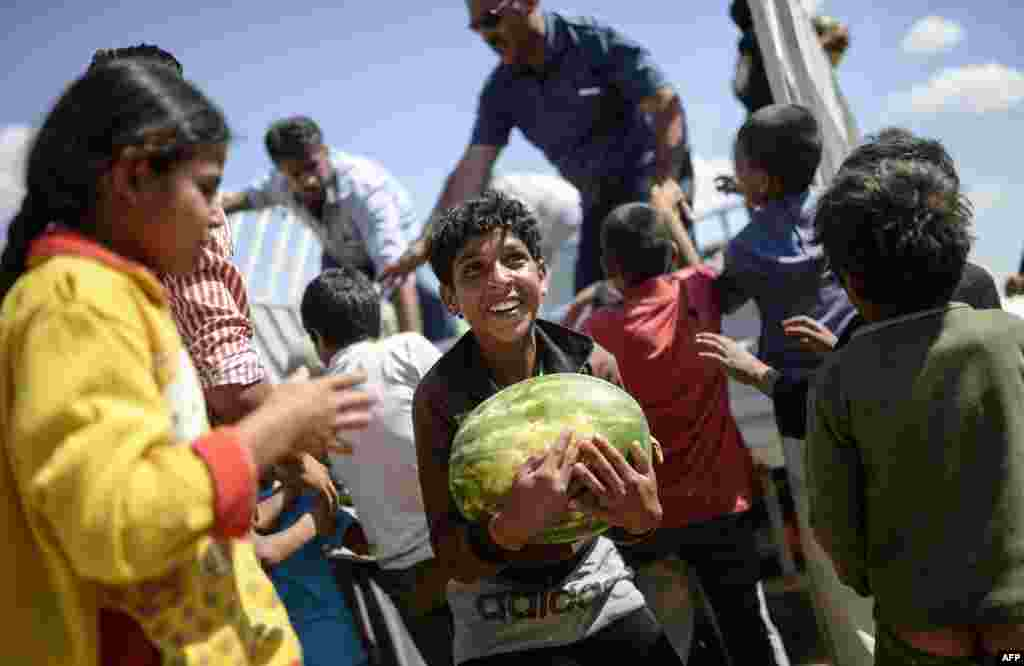 A Syrian boy holds a watermelon distibuted near the Akcakale crossing gate between Turkey and Syria at Akcakale in Sanliurfa province.