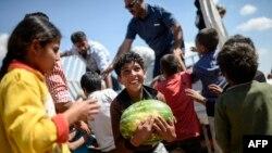 Anak pengungsi Suriah memegang semangka yang dibagikan dekat gerbang penyeberangan Akcakale antara Turki dan Suriah di provinsi Sanliurfa (16/6). (AFP/Bulent Kilic)