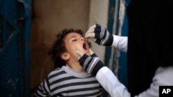 FILE - A Yemeni health worker administers a dose of polio vaccine to a boy during a house-to-house immunization campaign in Sana'a, Yemen, Feb. 21, 2017.