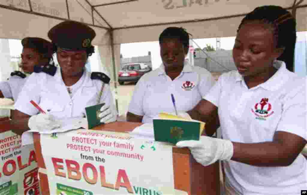 Jami'an kula da lafiyar matafiya na duba fasfo kafin su yi amfani da ma'aunin zafin jiki su yiwa Mahajjata gwajin cutar Ebola.